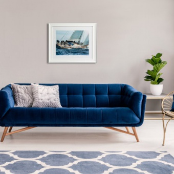 Royal blue couch with two pillows standing in real photo of bright living room interior with fresh plants, window with curtains, three paintings and carpet with moroccan trellis pattern
